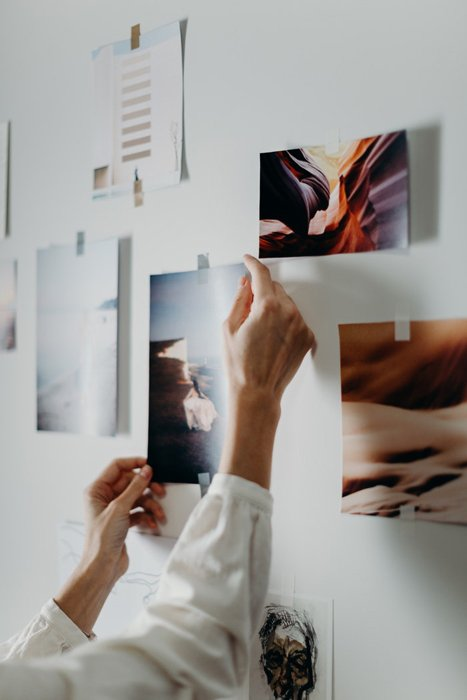 A person hanging photo prints on a wall