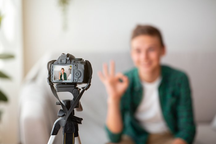 Selective focus on camera shooting teen guy showing okay gesture.