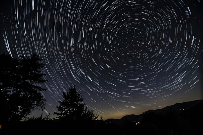 Star trail photograph around the North Polar star with hills, trees and house lights.