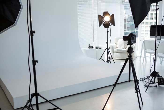 Empty photo studio with tripod, lighting equipment and digital camera