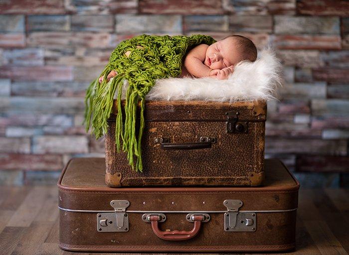 Little newborn baby sleeping on rustic suitcases