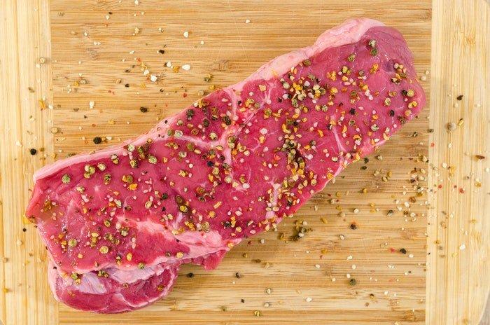 Flat lay of a seasoned cut of raw meat on a wooden board