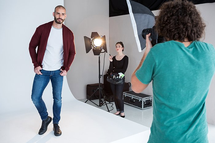 Model posing for a photoshoot in a photo studio with white background.