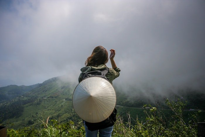 A girl stands in front of a mountainous landscape