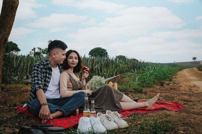 A couple having a picnic photoshoot under a tree