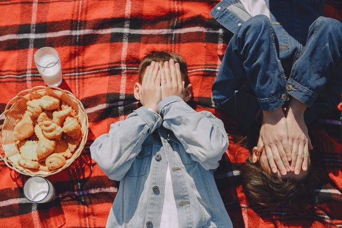 Overhead shot of playful kids on a picnic blanket