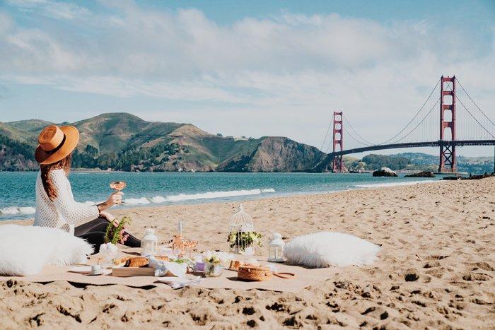 A girl posing for a lavish picnic photoshoot on a beach