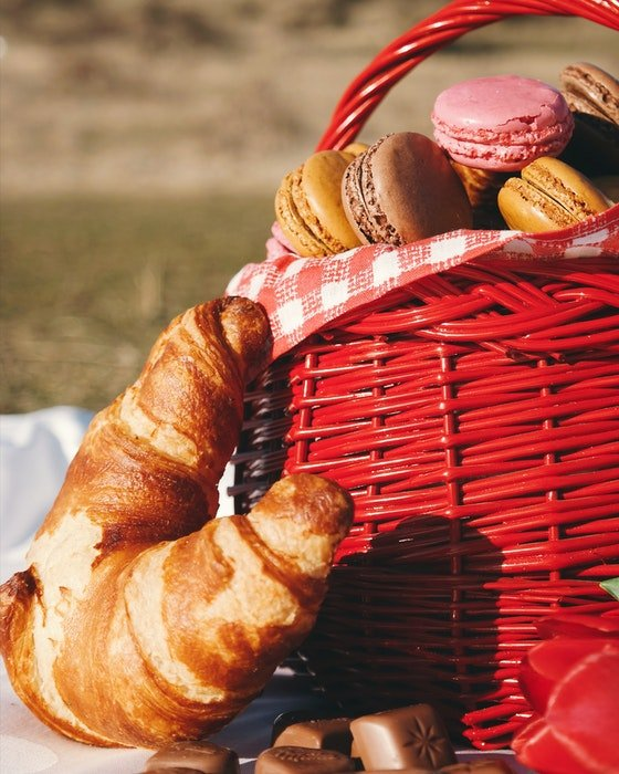 A close up of a red picnic basket full of macaroons and surrounded by croissants and chocolates