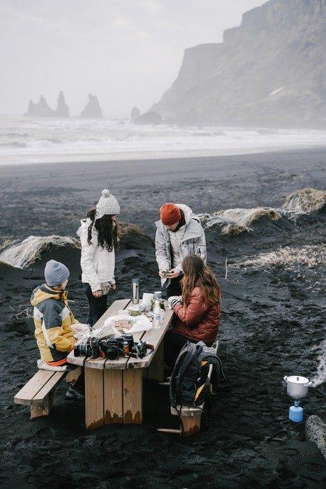A family having a picnic on a rocky misty beach