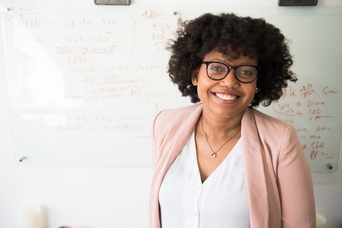 A headshot of a female in glasses by a whiteboard