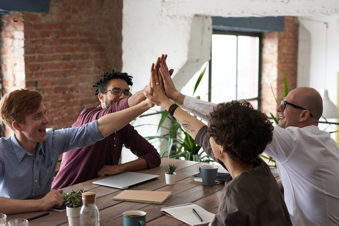 Four coworkers giving each other high-fives across a table