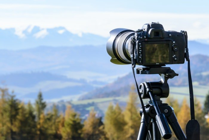 A DSLR on a tripod in front of a stunning landscape