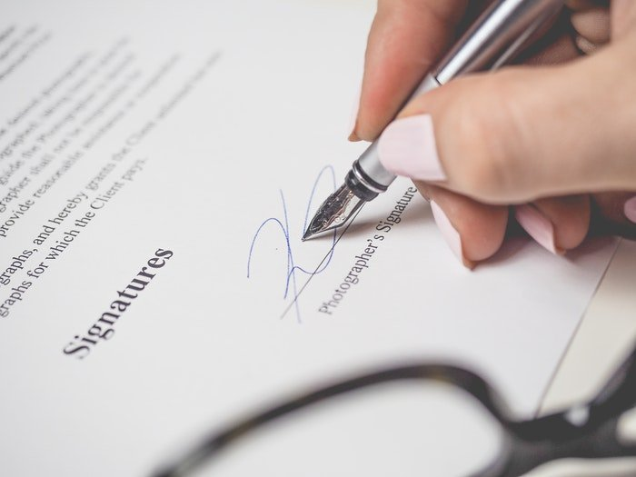 A close up of a person signing a stock photography contract