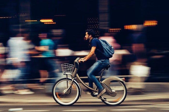 A man riding a bike past a busy marketplace