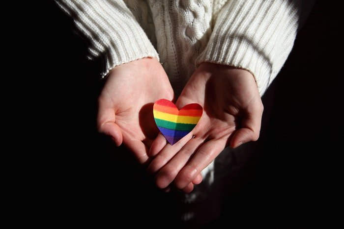 A close up of cupped hands holding a rainbow colored paper heart