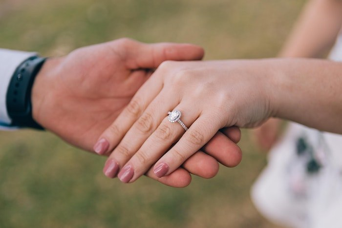 A wedding portrait closeup of the newlyweds holding hands outdoors