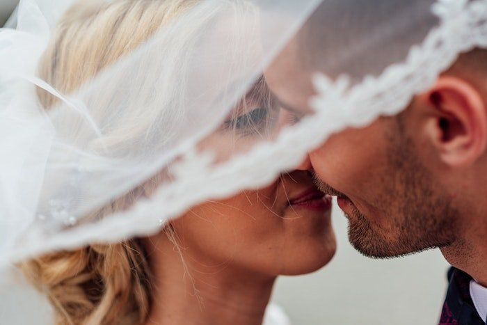 A wedding portrait closeup of the newlyweds kissing outdoors
