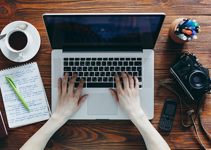 一张带有咖啡、笔记、笔记本电脑和相机的桌面图像。
