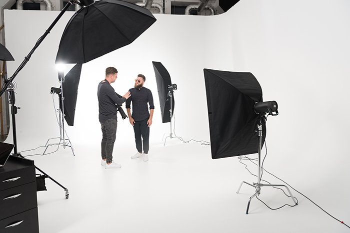 Two men standing in a photo studio with strobe lights.