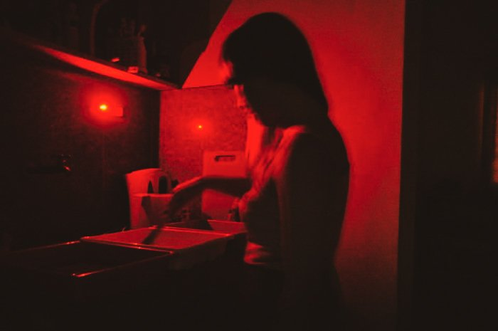 A person in a photography darkroom