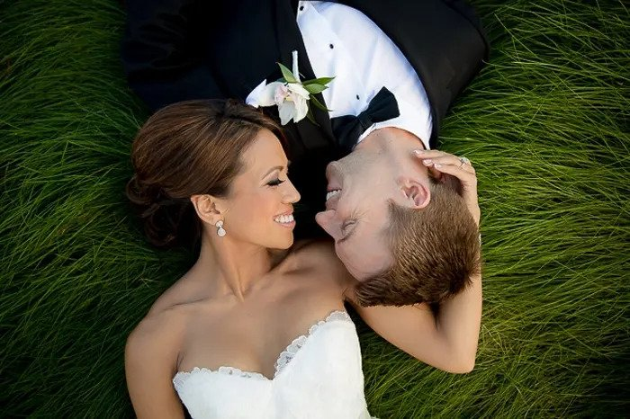 Wedding portrait of the newlywed couple lying on the grass