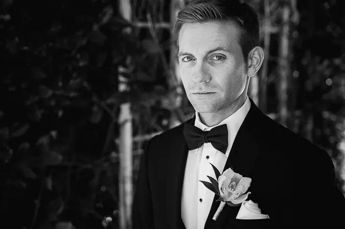 A black and white portrait of a man in a tuxedo