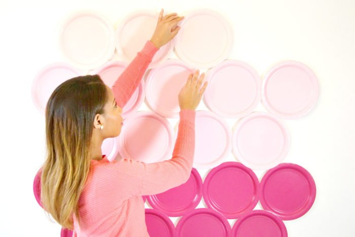 A person hanging pink plates as a DiY photography background