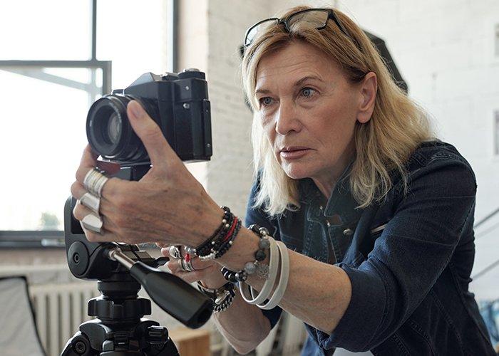 Women adjusting camera exposure settings.