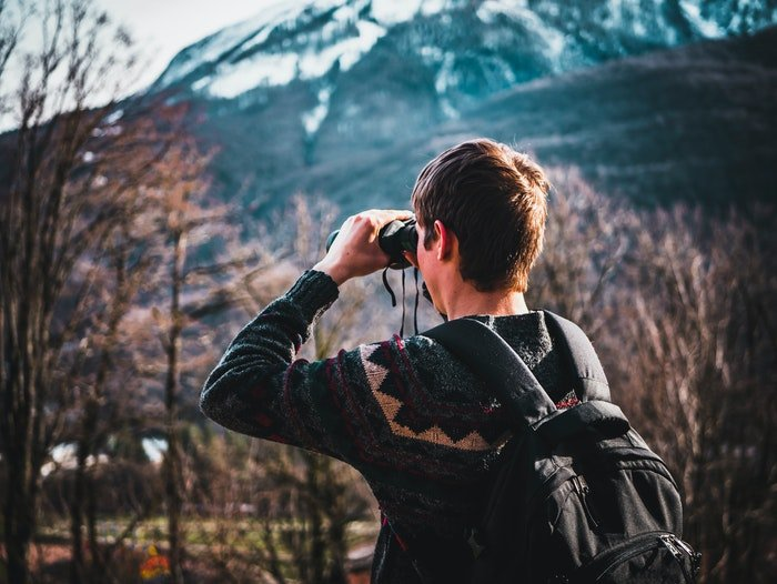 A man using binoculars outdoors