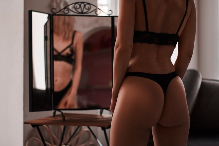 A blonde model in lingerie posing in front of a mirror
