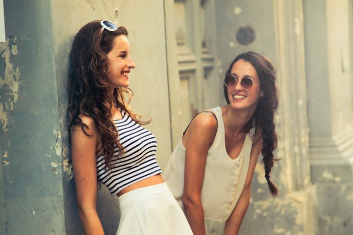 Candid portrait of two girls chatting outdoors