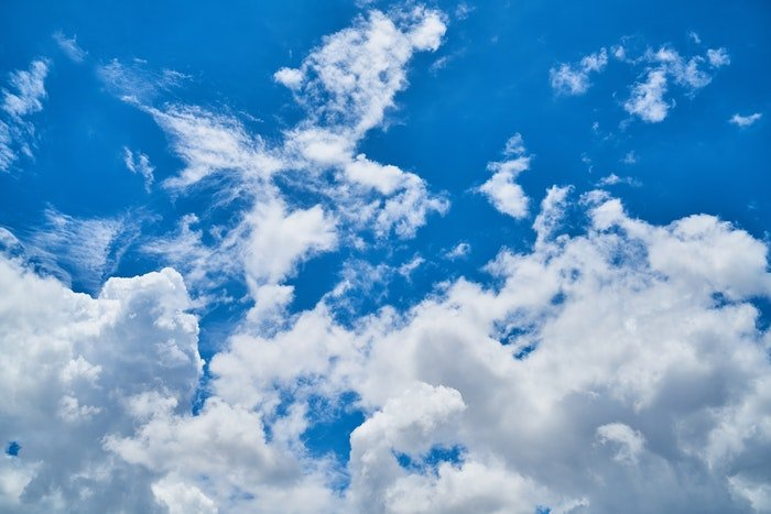 photo of fluffy clouds in the bright blue sky