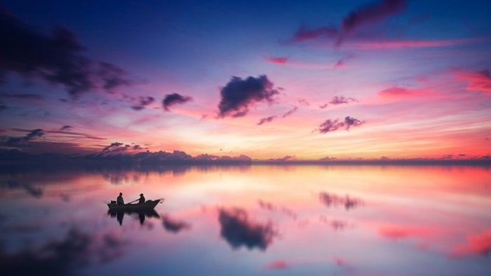 Colorful clouds above a lake with the silhouette of a boat