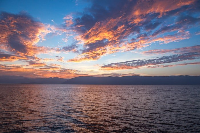 photo of clouds and sunset above a huge waterscape