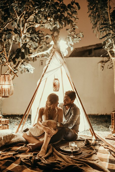 A couple embracing in front of a teepee