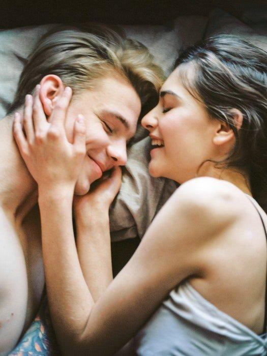 Close up couples boudoir portrait embracing on a bed