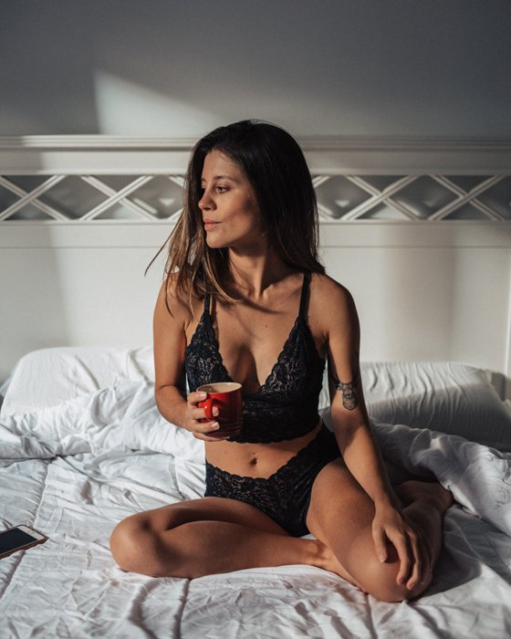 Beautiful DIY boudoir photo of a girl in lingerie posing on a bed