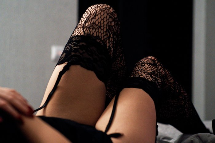 Close up DIY boudoir photo of a girl in black suspender stockings and lingerie posing on a bed