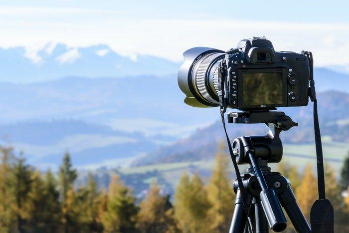 A camera on a tripod with a mountain landscape