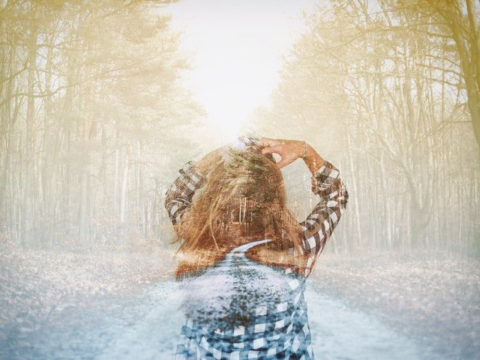 A double exposed image of a girl walking through a forest