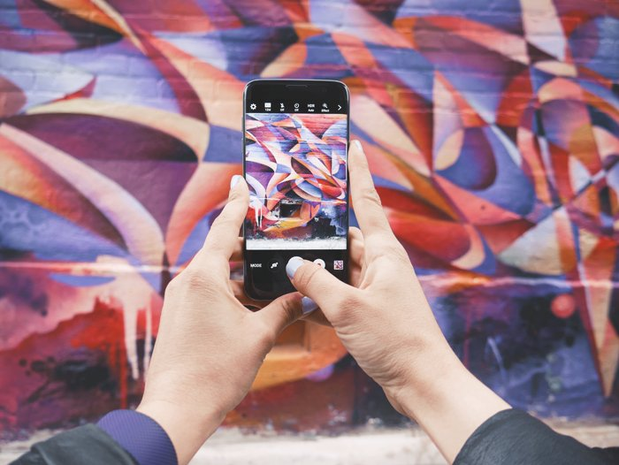 photo of someone taking a photo of a colorful wall with a smartphone