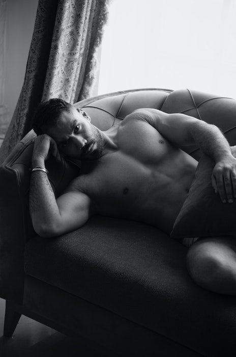 Black and white boudoir photo of a male model lying on a sofa