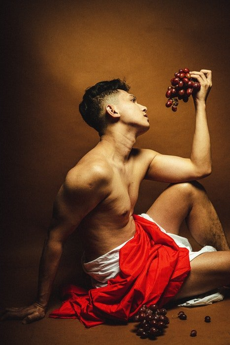 Photo of a male model in an ancient Greek-style pose with a grape