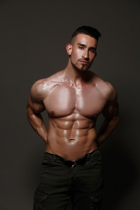 Boudoir photo of a half-naked male model standing in fron of a neutral background