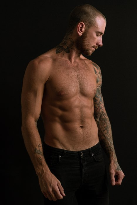 photo of a half naked male model with a black background