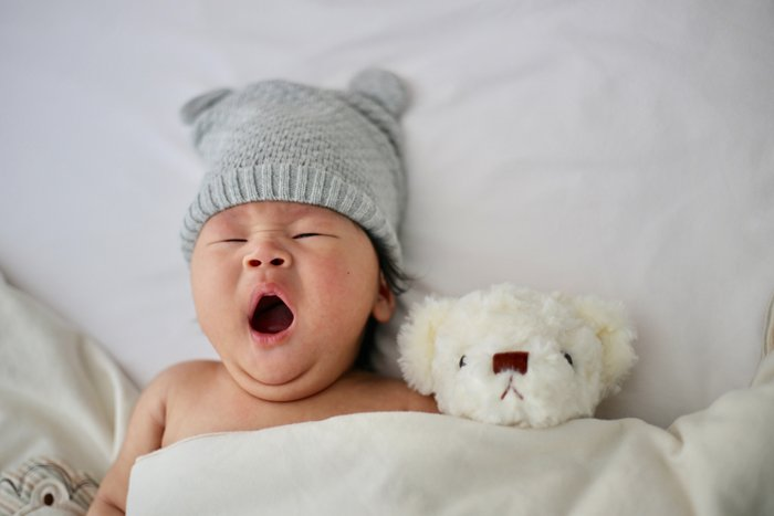 photo of a newborn baby in cute outfit posed with a teddy bear