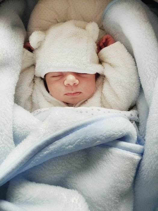 photo of a newborn in a cute hat with bear ears