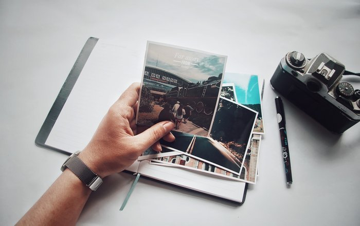 A person holding printed photos
