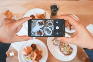photo of hands holding a smartphone to take photo of plates of food