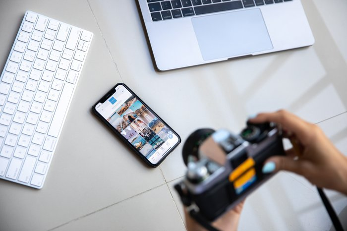 A person taking a photo of a smartphone with a film camera